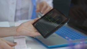 医生审查在片剂的耐心心电图,护士写医生的忠告 股票视频