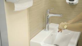 医生小心地洗有抗菌肥皂的手在水在轻拍下和抹下强的小河在诊所的户内 股票录像