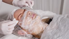 医生应用在他患者说谎的面孔的麻醉的奶油 影视素材
