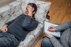 医生拜访他的患者 病的哀伤的人谈话与关于他的问题的医生 医生写笔记 图库摄影