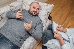医生拜访他的患者 病的哀伤的人谈话与关于他的问题的医生 免版税库存图片