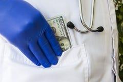 医生掩藏或制定在白色博士外套的口袋的一百元钞票 概念照片贿款,在医学,paym的腐败 免版税库存图片