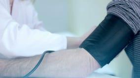 医生是在一间医疗屋子测量在一名患者的压力的妇女 股票视频