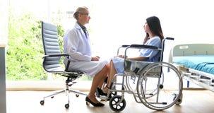 医生是询问和解释病症对轮椅的一名女性患者在医院 免版税库存图片