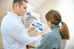 医生显示患者一个X-射线图象 免版税库存图片