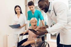 医生显示某事在片剂给一名年长患者在老人院 库存图片