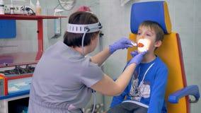 医生检查男孩喉头在明亮的光下 股票录像