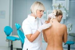 医生检查的皮肤妇女 免版税库存照片