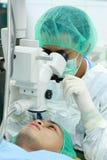 医生检查的眼睛患者 免版税库存图片