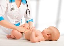 医生检查,按摩婴孩肚子 免版税图库摄影