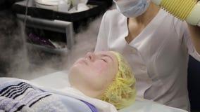 医生洗涤与蒸汽的妇女的皮肤 有问题皮肤的年轻女人在美容师 整容术概念 股票录像