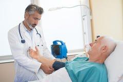 医生测试血压前辈患者 免版税库存图片