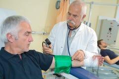 医生测量的血压前辈患者 库存照片