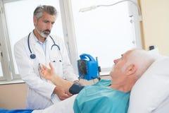 医生测量的血压老人人 免版税库存图片