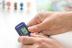 医生测量的kid& x27; s氧气与手指oxymeter显示器的饱和水平 医疗保健,健康显示 免版税库存图片