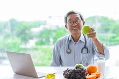 医生用果子推荐吃健康饮食纤维低脂肪绿色苹果和牛奶 库存照片