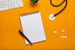 医生的书桌顶视图有听诊器键盘笔记薄的和笔、处方和药片 免版税库存图片