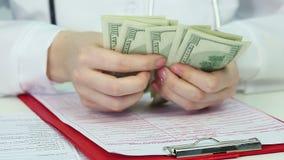 医生的手特写镜头计数美元,腐败卫生保健系统,贿赂的 股票视频