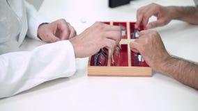 医生眼科医生帮助一个客户选择在眼科诊所的最适当的玻璃 股票录像