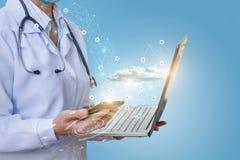 医生研究电话和膝上型计算机在医疗网络 免版税库存图片