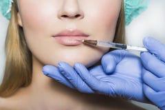 医生美学家做嘴唇更正和增广给女性患者 免版税库存照片