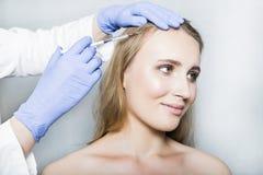医生美学家做顶头秀丽射入给女性患者在白色背景 库存图片