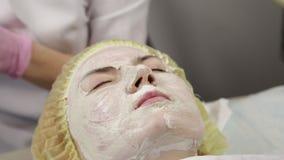医生美容师从患者的面孔去除白色面部洗涤的面具 股票录像