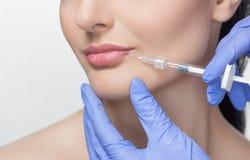 医生美容师做嘴唇增广做法美容院的一名美丽的妇女 库存图片