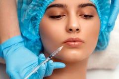 医生美容师在做拉紧和使的皱痕光滑使充满活力的面部射入方法 库存图片