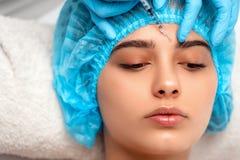 医生美容师在做拉紧和使的皱痕光滑使充满活力的面部射入方法 免版税库存图片