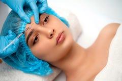 医生美容师在做拉紧和使的皱痕光滑使充满活力的面部射入方法 免版税库存照片