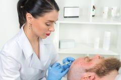医生美容师在面孔皮肤做拉紧和使的皱痕光滑使充满活力的面部射入方法 免版税图库摄影