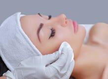医生美容师洗涤与补品一个美丽,少妇的面孔皮肤美容院的 图库摄影