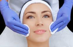 医生美容师洗涤与补品一个美丽,少妇的面孔皮肤 库存图片