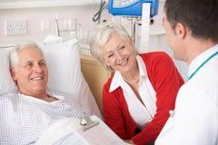 医生联系与高级夫妇在医院 免版税库存图片