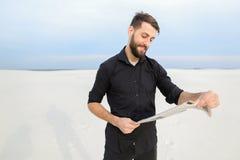 医生读书报纸在乡下 免版税库存图片