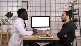 医生谈话与他的男性患者 空白显示 免版税库存照片