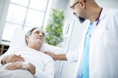 医生谈话与患者在医院病床上 免版税库存图片
