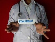 医生身分,拿着在红色背景的投资纸文本 医疗和医疗保健概念 库存图片