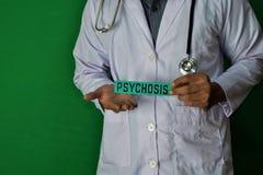 医生身分,拿着在绿色背景的精神病纸文本 医疗和医疗保健概念 免版税库存照片