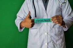 医生身分,拿着在绿色背景的退伍军人健康纸文本 免版税库存图片