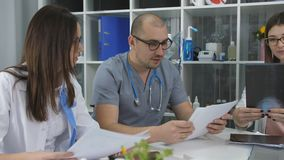 医生队开会议在办公室 书桌的三位医生在忠告办公室 股票视频