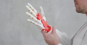医生骨科医师进行设法机器人义肢的手测试移动手指,做姿态 股票录像