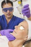 医生&激光在高级妇女的皮肤处理 免版税库存照片