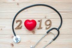 医疗保健、健康和医疗概念的2019新年快乐 有红心和木数字的听诊器在桌上 库存图片