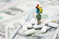 医疗保健和医学工业企业概念,拿着气球的微型人人站立在美国的白色片剂药片 免版税库存图片