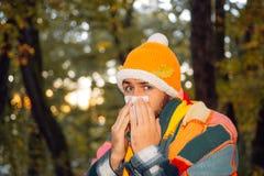 医疗保健和医学概念-有纸组织的不适的人在秋天公园 遭受寒冷的夹克的成熟人 免版税库存图片