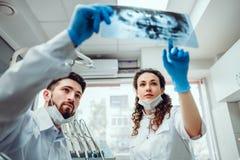 医疗保健,医疗和放射学概念-看X-射线的两位牙医医生 r 免版税库存照片
