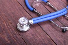 医疗在木背景隔绝的听诊器和片剂 库存照片