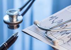 医疗工具 听诊器和心电图在桌上 库存图片
